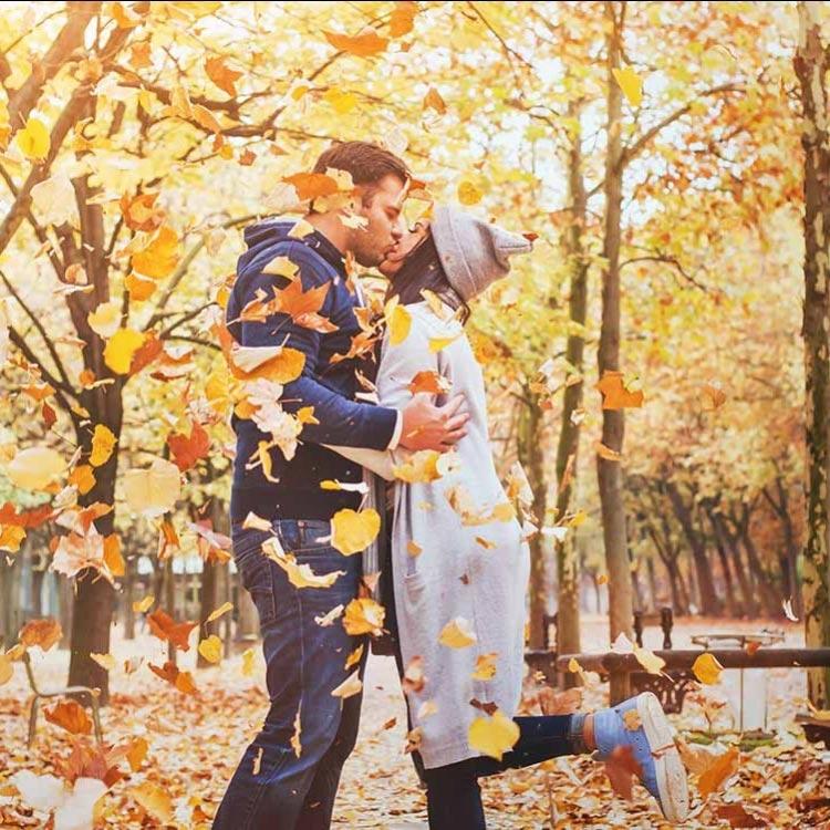 paar-küsst-sich-draußen-im-herbst-mit-laub-und-blättern