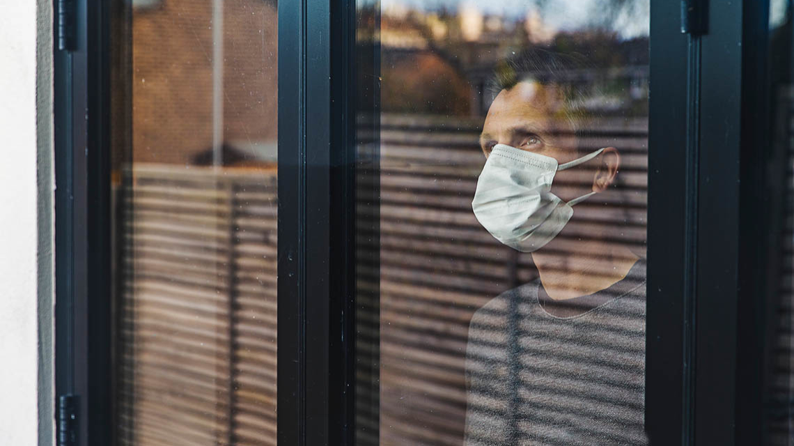 Mann mit Mundschutz schaut aus dem Fenster und sieht traurig aus