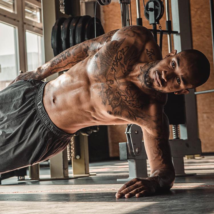 Junger sportlicher muskulöser Mann macht Side Plank im Fitnessstudio