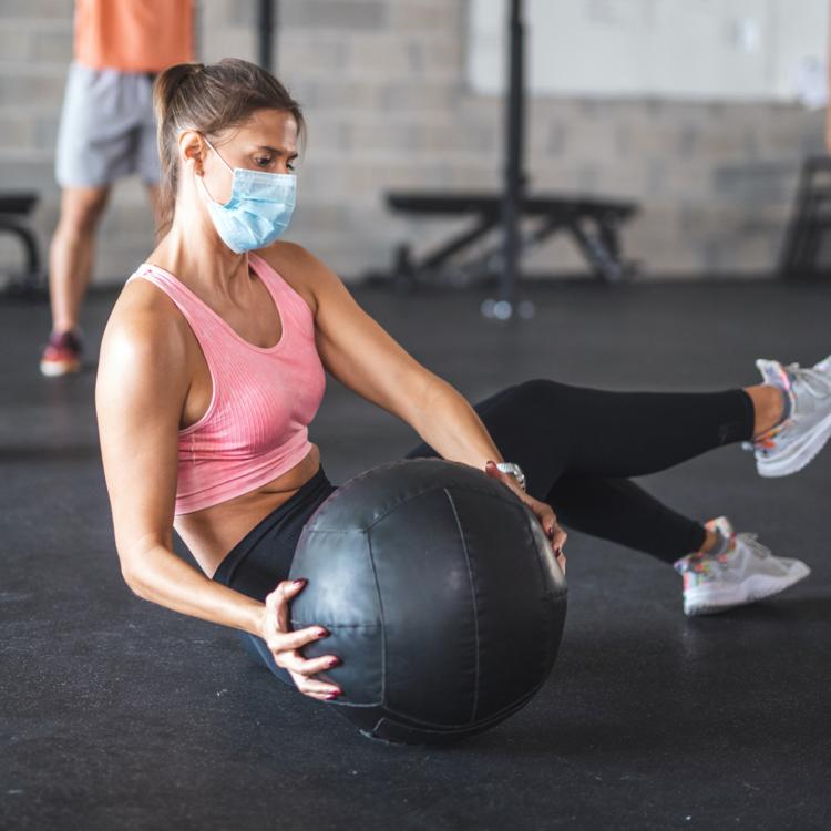 Junge sportliche Frau trägt Mundschutz und macht Übungen mit einem Ball auf dem Boden eines Fitnessstudios