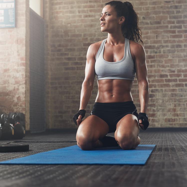 Durchtrainierte sportliche muskulöse Frau kniet im Fitnessstudio auf einer Matte neben Kettlebells