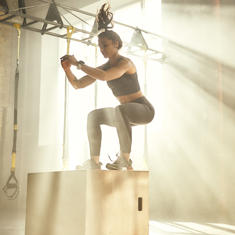 Sportliche Frau springt auf eine Box