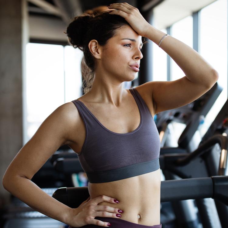 Frustrierte Frau in Trainingskleidung steht auf dem Laufband im Fitnessstudio und fasst sich an den Kopf